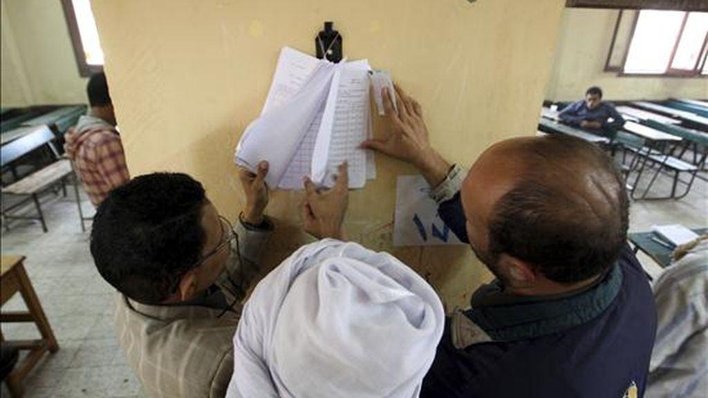 Tres hombres buscan sus nombres en una lista instalada en un colegio electoral durante la segunda vuelta de las elecciones parlamentarias en un colegio electoral en El Cairo, Egipto, ayer. EFE