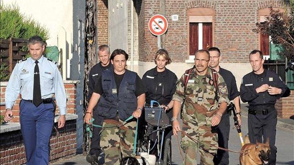 Miembros de la Gendarmería francesa llegan con perros especiales al lugar en donde una pareja fue arrestada después de encontrar los cuerpos de ocho bebés enterrados en el jardín de su casa en Villers-au-Tertre. EFE