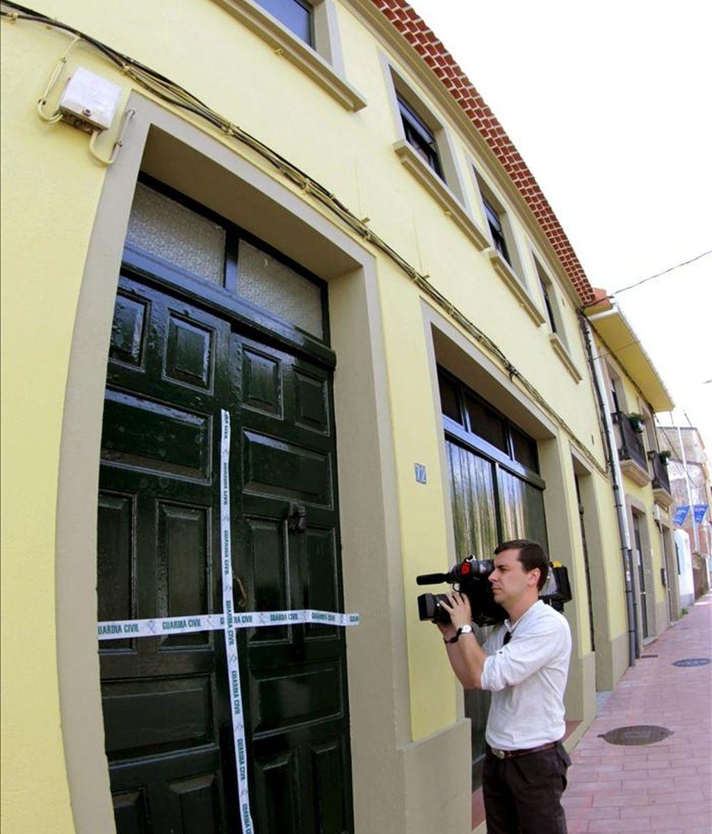 Un reportero toma imágenes de la puerta precintada de la vivienda de la población coruñesa de Noia donde una joven de 19 años apareció ayer muerta, brutalmente acuchillada. EFE