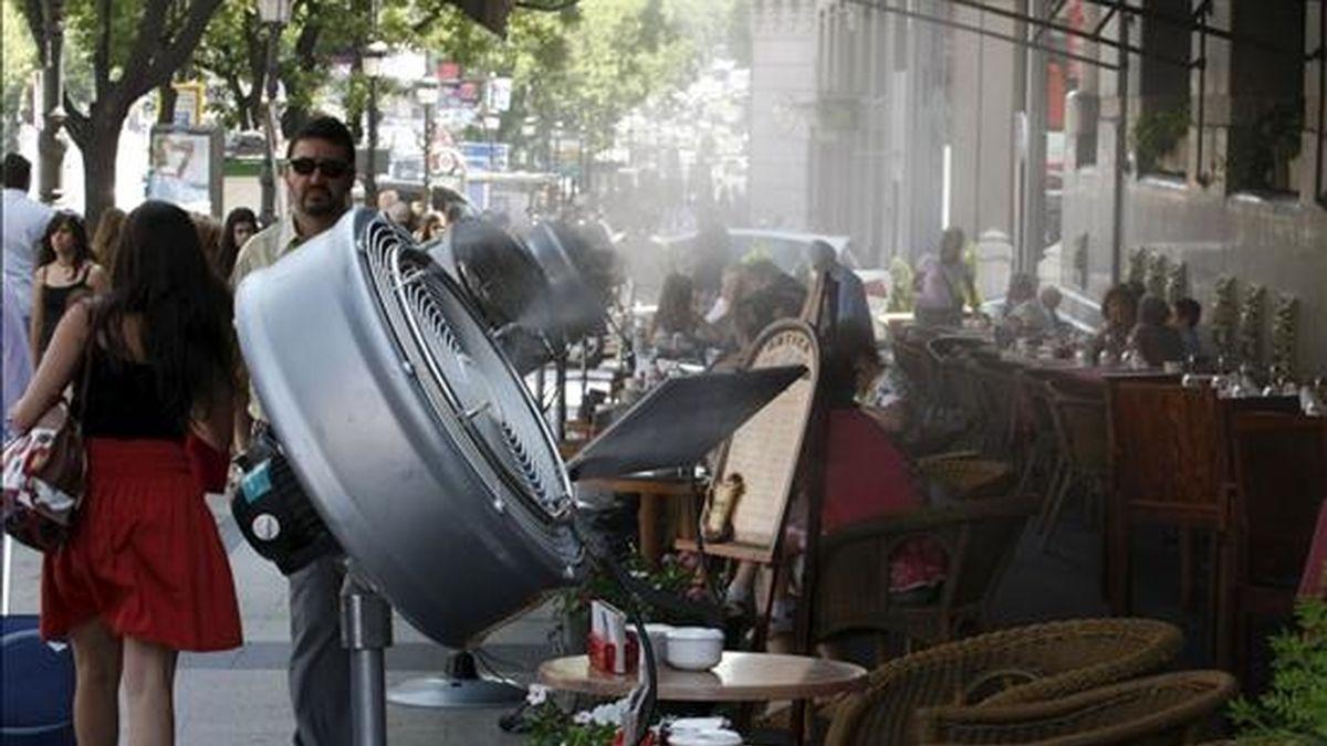 Los clientes de la terraza del Círculo de Bellas Artes, situada en la madrileña calle de Alcalá, disfrutan de unos momentos refrescantes gracias a los ventiladores que distribuyen agua pulverizada sobre las mesas, para aliviar los efectos de la ola de calor. EFE