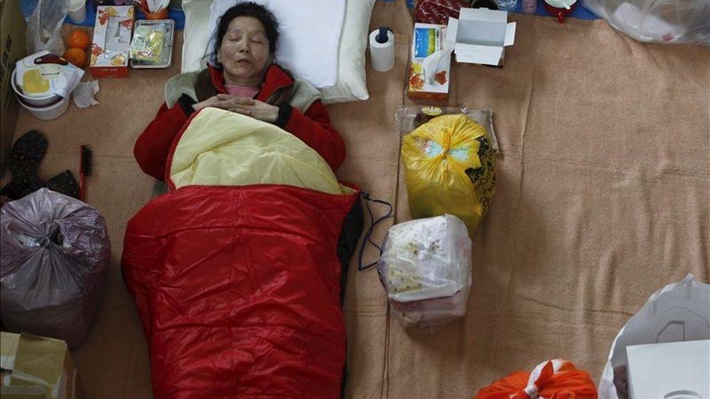 Una mujer descansa en una bolsa de dormir en un centro de evacuación, en la ciudad costera de Ishinomaki, que fue devastada por el tsunami del pasado 11 de marzo, en la provincia de Miyagi, al noreste de Japón. EFE