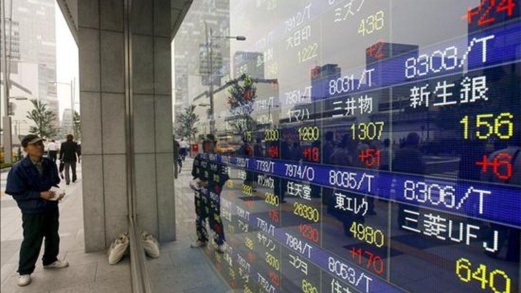 Un hombre pobserva una pantalla en la que se muestran los precios de las acciones, en Tokio. EFE/Archivo