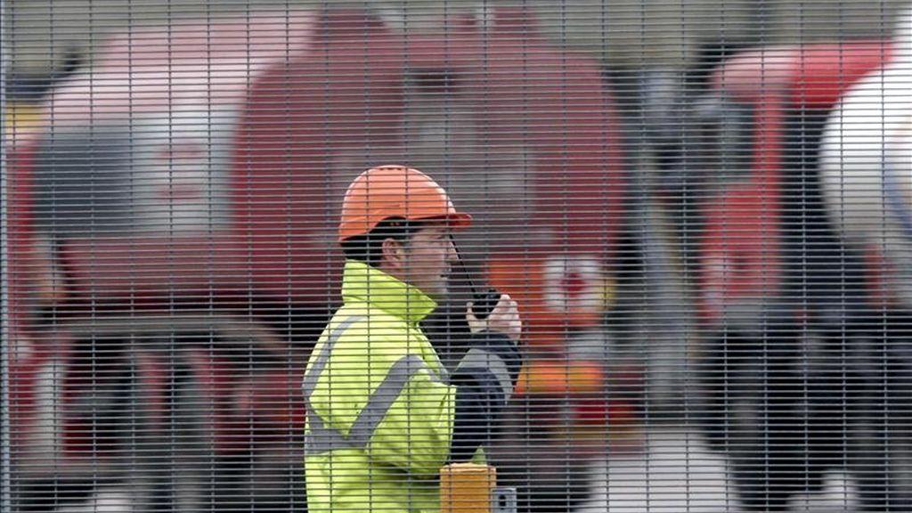 """Un operario habla por un """"walkie-talkie"""" mientras unos camiones cisterna esperan para cargar gasolina en el depósito de combustible de Kingsbury, Reino Unido. EFE/Archivo"""