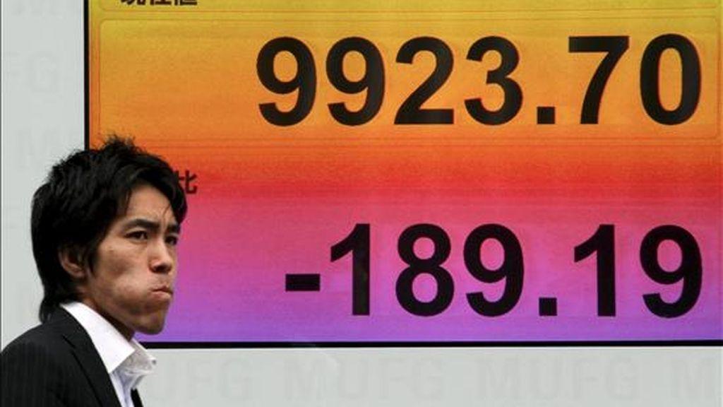 Un empresario pasa junto a una pantalla electrónica con los resultados de la Bolsa de Tokio. EFE/Archivo