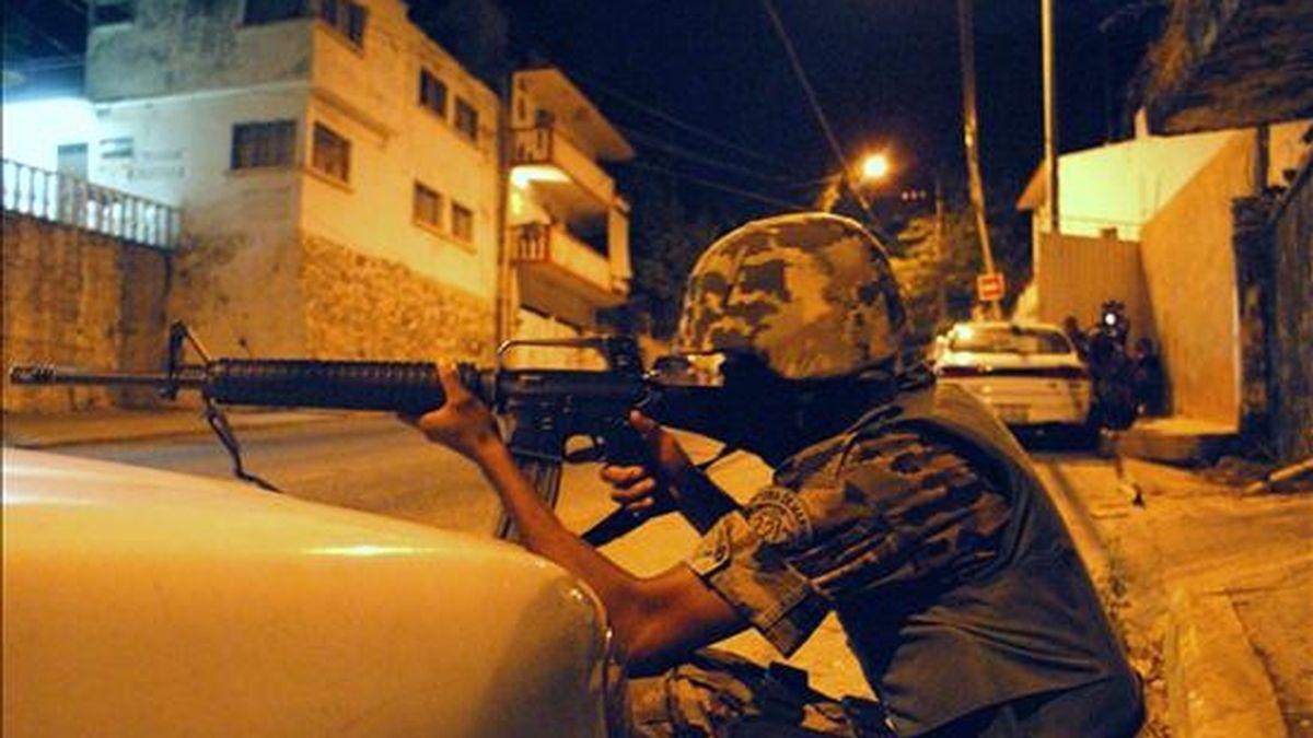 Un soldado del Ejército apunta contra un grupo de sicarios durante un tiroteo que duró cerca de cinco horas y en el que murieron 18 personas en el puerto turístico de Acapulco. EFE