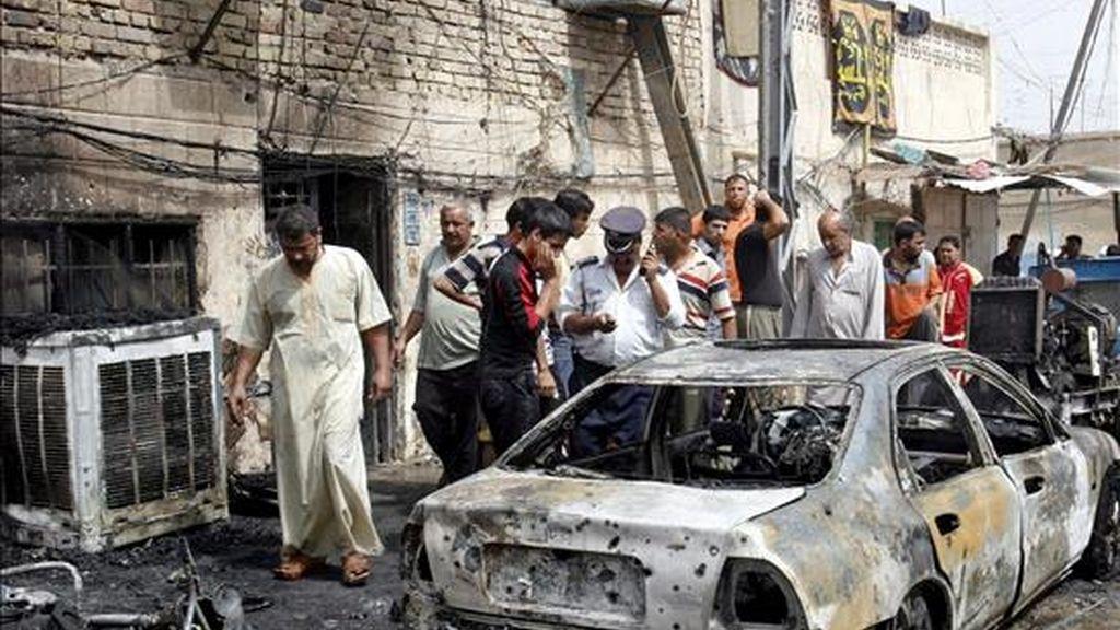 Un grupo de personas observa un coche destrozado tras un atentado en el distrito de Sader en Bagdad. EFE/Archivo