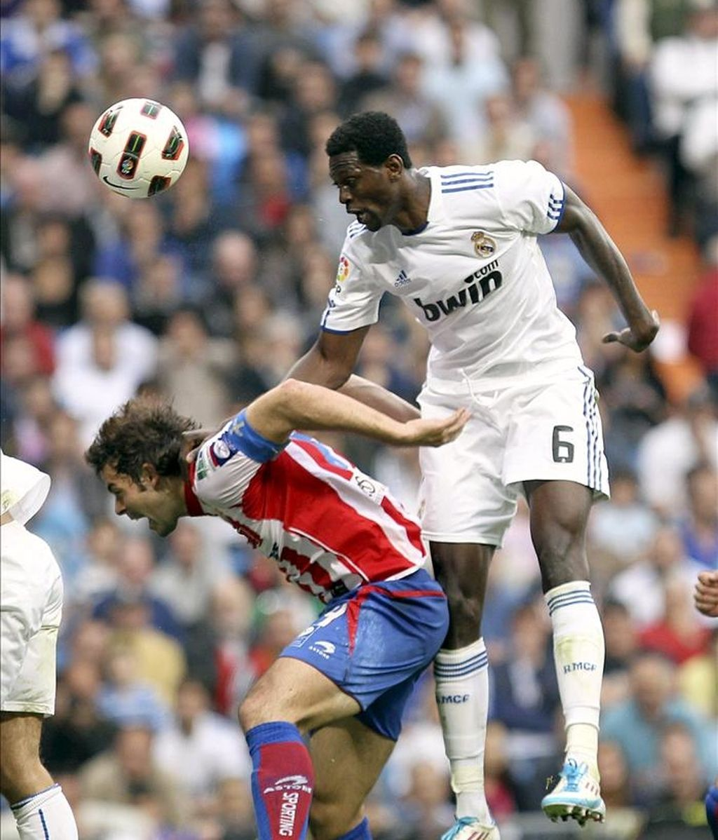 El delantero togolés del Real Madrid Emmanuel Adebayor (d) remata de cabeza un balón ante el defensa del Sporting de Gijón Iván Hernández durante el partido correspondiente a la trigésima jornada de Liga de Primera División que ha enfrentado a ambos equipos esta tarde en el estadio Santiago Bernabéu. EFE