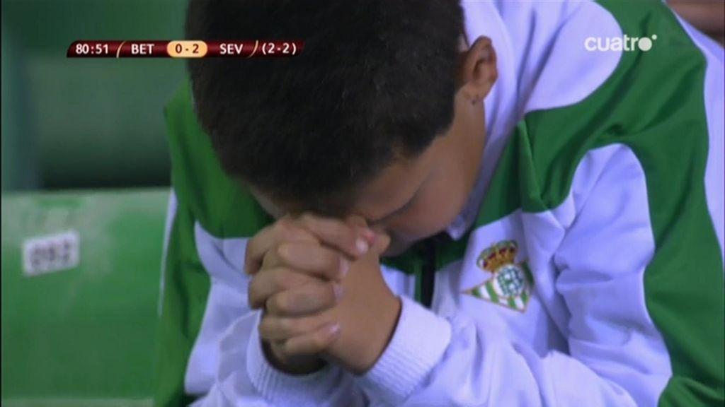 Un niño reza en la grada del Villamarín