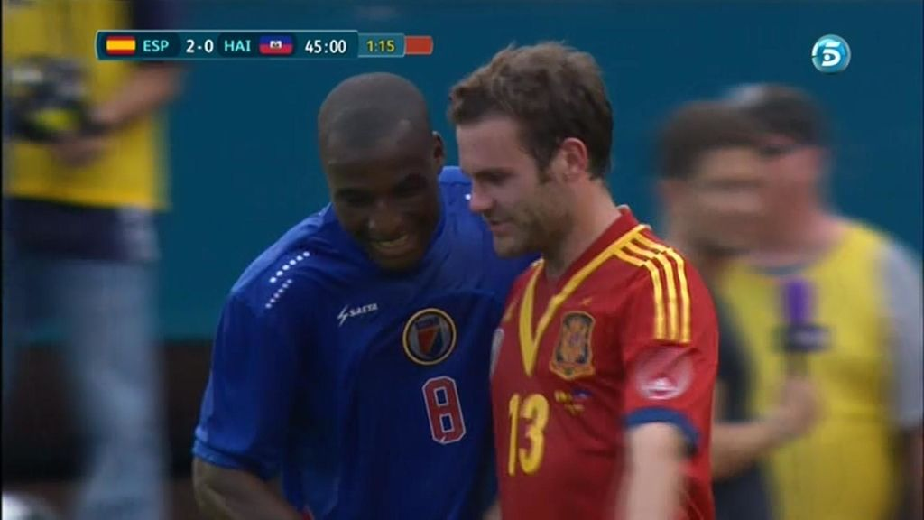 Juan Mata habla con un jugador de la selección de Haití