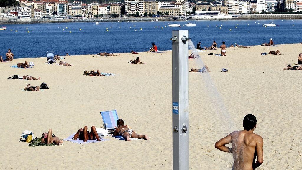 Numerosas personas disfrutan hoy en la playa de Ondarreta de San Sebastián, donde a pesar de estar ya en otoño se registran temperaturas veraniegas.
