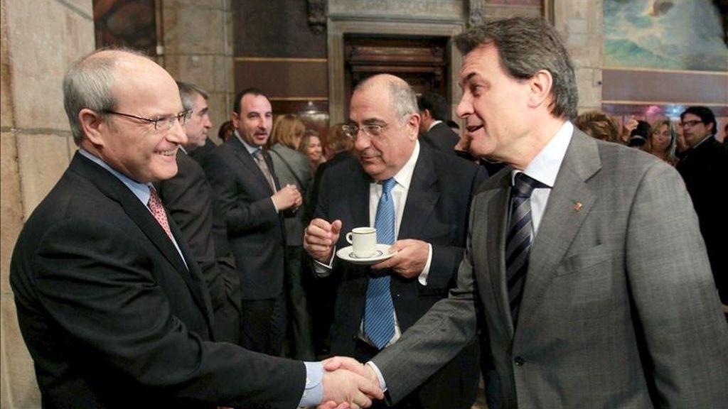 El presidente catalán, Artur Mas (d), que protagonizó hoy su primer Sant Jordi como jefe del ejecutivo con una austera recepción en el Palau de la Generalitat, saluda al expresidente, José Montilla (i), ante la presencia del lider de la oposición, el socialista Joaquim Nadal (c). EFE