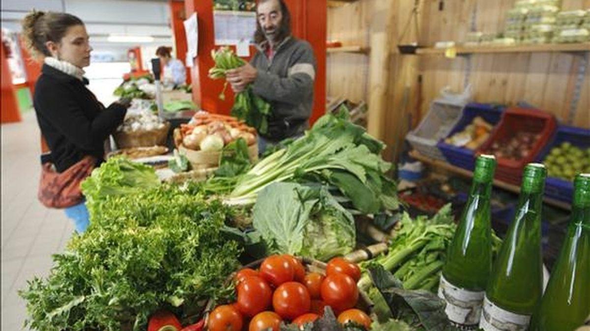 Un comerciante atiende a una clienta en su puesto de verduras. EFE/Archivo