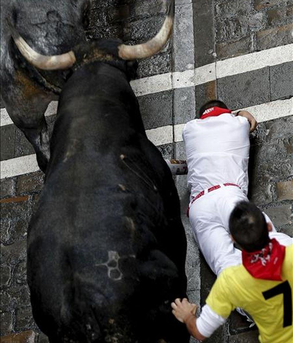Un mozo en el suelo junto a un toro de la ganadería sevillana de Miura, en el tramo de la Calle Estafeta durante el quinto encierro de los Sanfermines del 2010. EFE