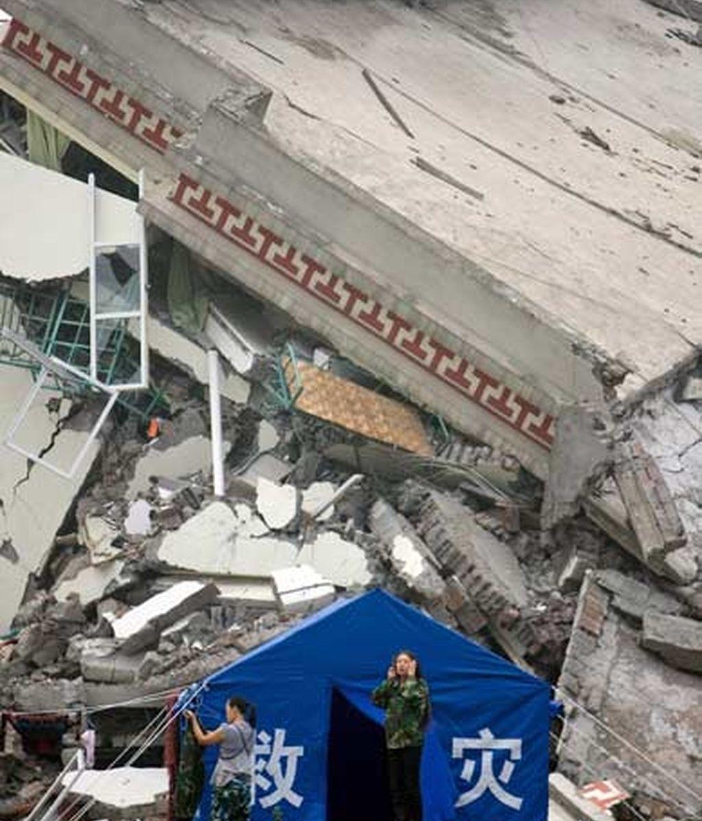 Voluntarios permanecen junto a una carpa provisional ubicada frente a una edificación destruída. Foto: EFE