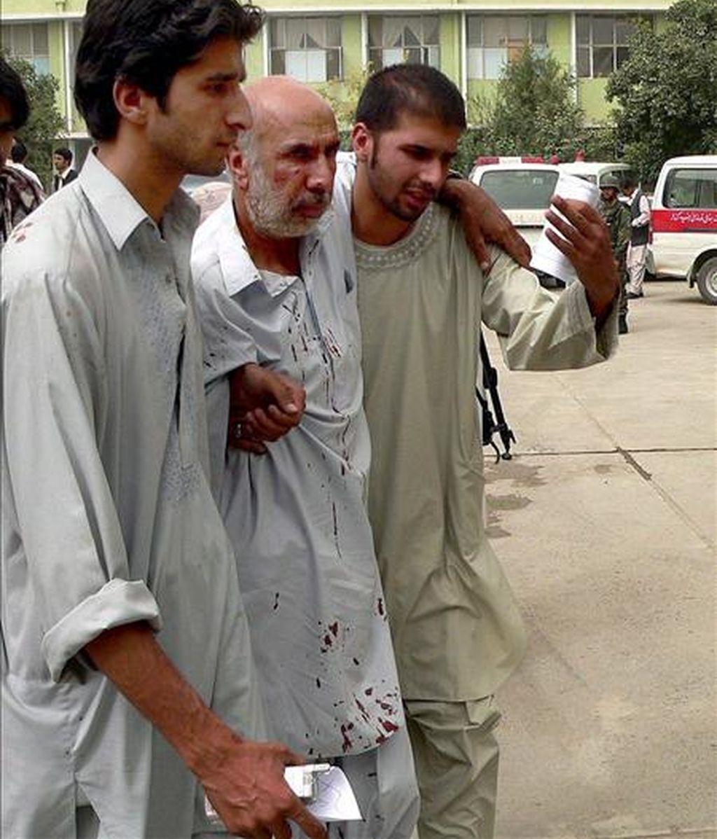 Dos jóvenes ayudan a un herido después de un doble ataque suicida contra una comisaría de la sureña ciudad de Kandahar (Afganistán). EFE/Archivo