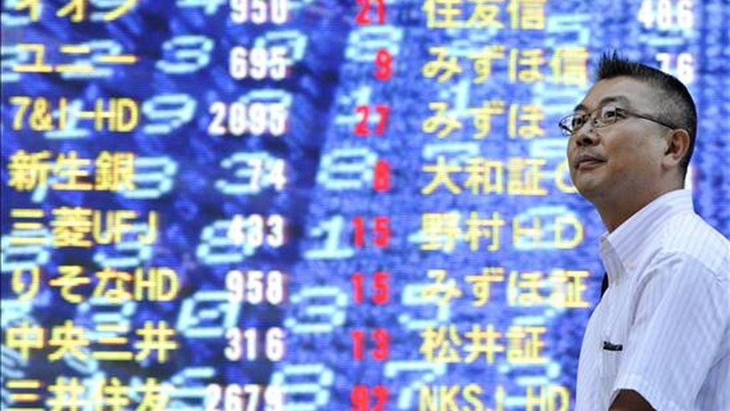 Un ejecutivo japonés camina frente a un tablero electrónico con los índices de la Bolsa de Tokio, Japón. EFE/Archivo