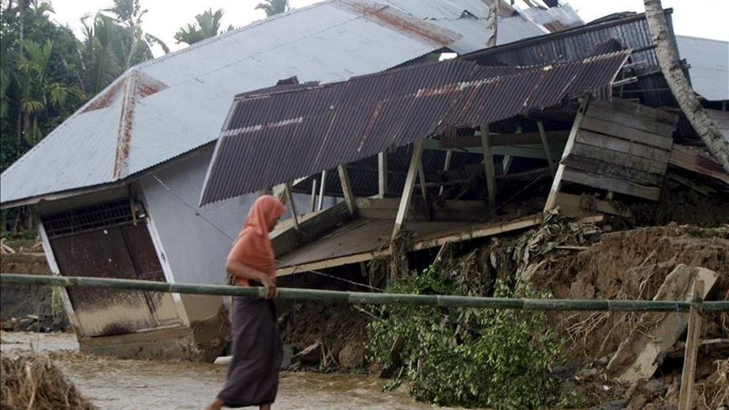 Una lugareña cruza por un puente junto a una casa dañada por las inundaciones en la localidad de Tangse, en Aceh (Indonesia) el pasado 11 de marzo. EFE/Archivo
