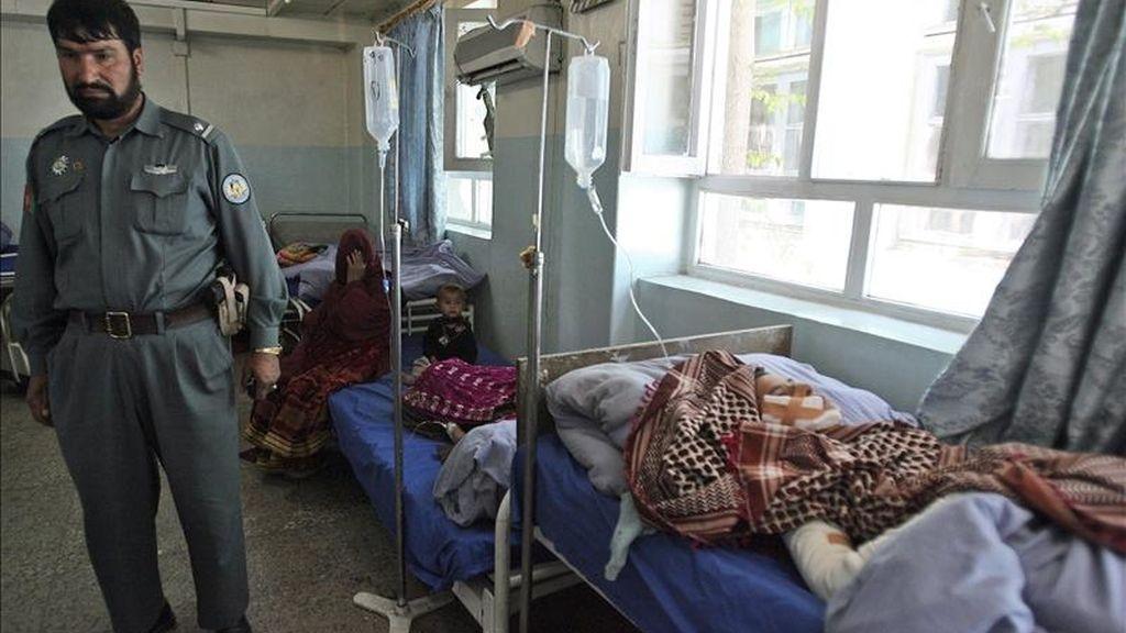 Un policía afgano permanece junto a varias personas que resultaron heridas en un atentado perpetrado en Ghazni (Afanistán). EFE
