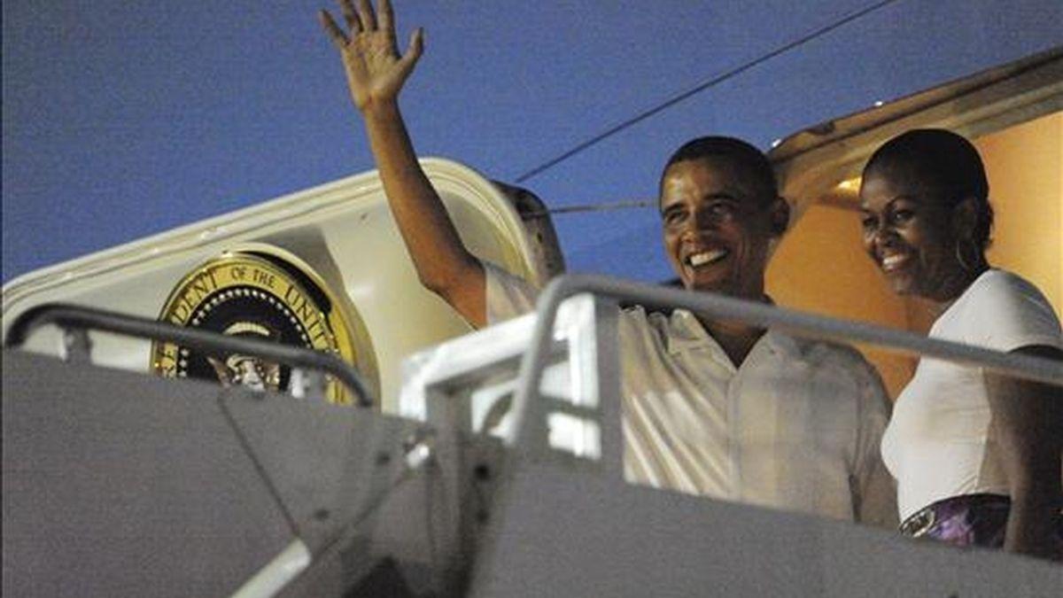 El presidente de EEUU, Barack Obama (i) y su esposa Michelle (d), saludan antes de abordar al avión que los traslada a Washington tras sus vacaciones, en Honolulu, Hawai (Estados Unidos). Tras diez días de descanso en su estado natal, Obama retomará la actividad con una reunión con su secretario de Defensa, Robert Gates. EFE