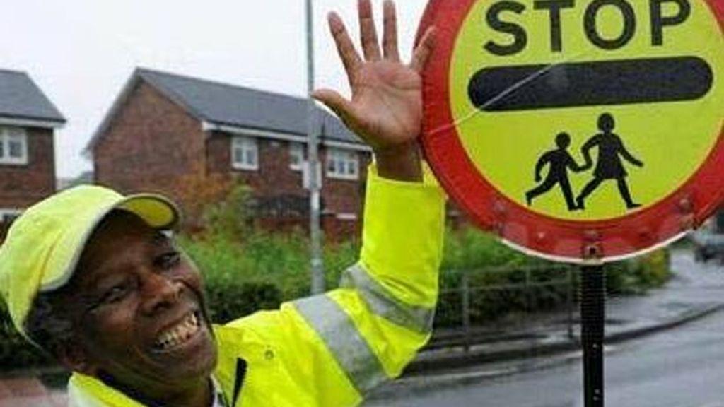 Prohiben a un hombre que regula el tráfico chocar la mano a los escolares