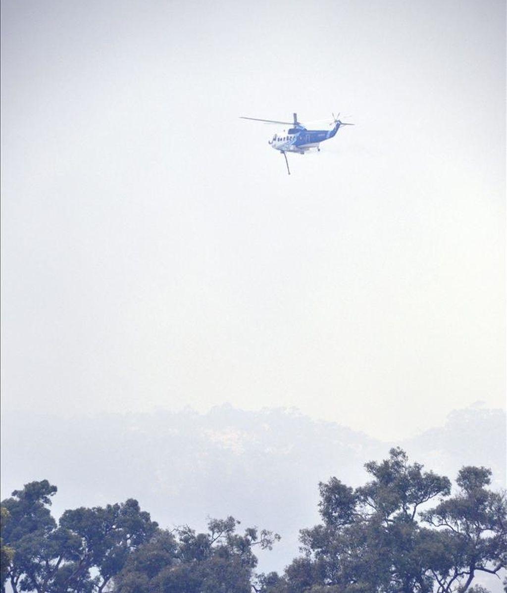 Un helicóptero lucha hoy contra el rápido avance de un incendio fuera de control cerca de Perth, ubicada en el estado de Australia Occidental. EFE