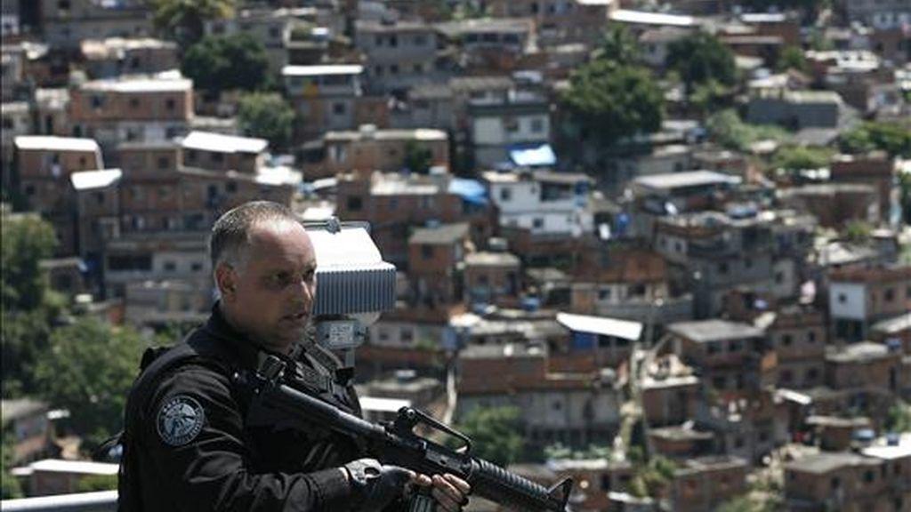 Un policía monta guardia en el Complexo do Alemao donde las fuerzas de seguridad izaron la bandera de Brasil para simbolizar la toma de ese conjunto de favelas en Río de Janeiro (Brasil) que hasta esta mañana era dominado por narcotraficantes. EFE