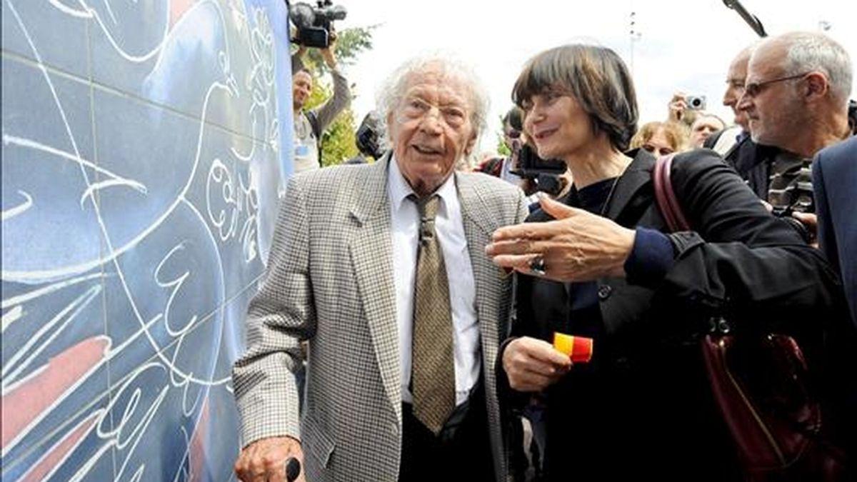 El artista suizo Hans Erni y la ministra suiza de Exteriores, Micheline Calmy-Rey, durante la inauguración los frescos que decoran la entrada de la sede de la ONU en Ginebra. EFE