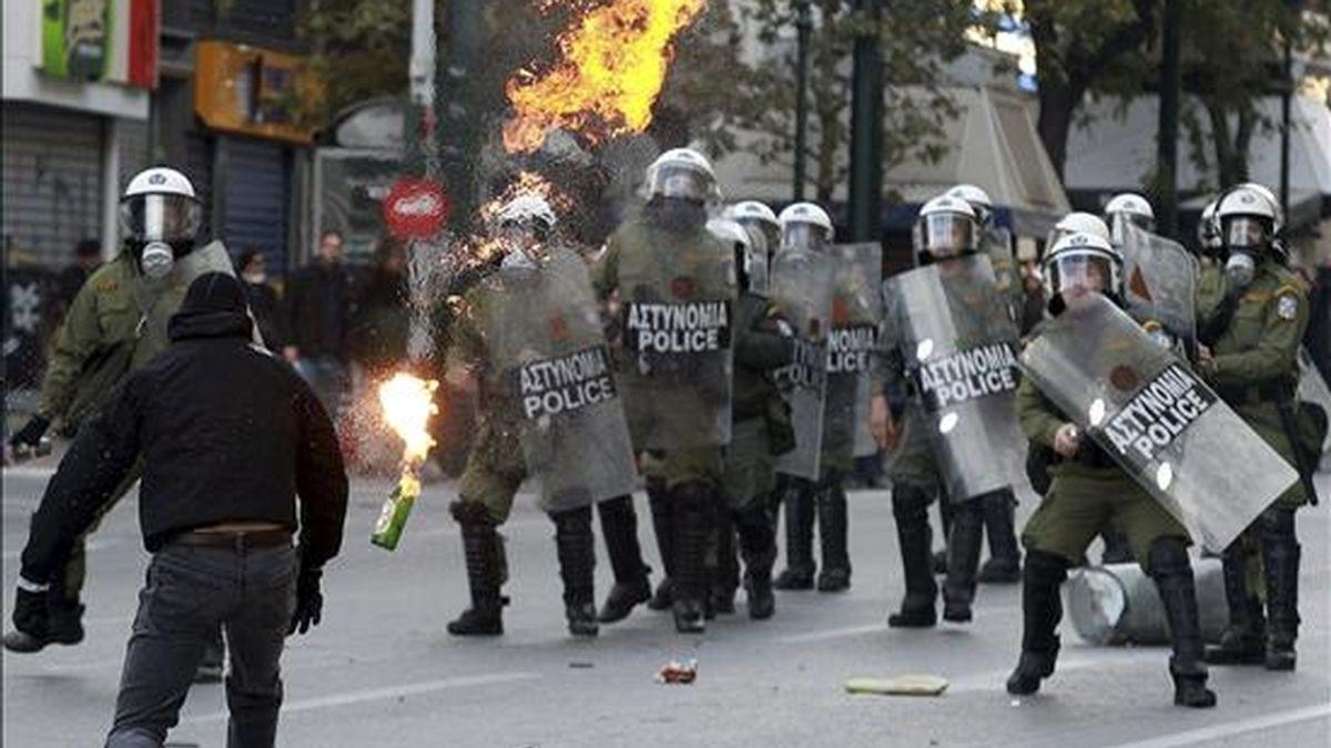 Un joven encapuchado lanza una bomba casera contra policías antidisturbios durante una manifestación con motivo del segundo aniversario del asesinato del adolescente Alexandros Grigoropoulos a manos de un policía, en el centro de Atenas, Grecia. EFE