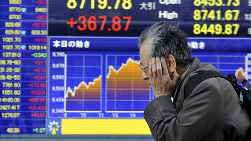 Un hombre camina cerca de un panel electrónico que muestra los valores de la bolsa de Tokio, Japón. EFE/Archivo