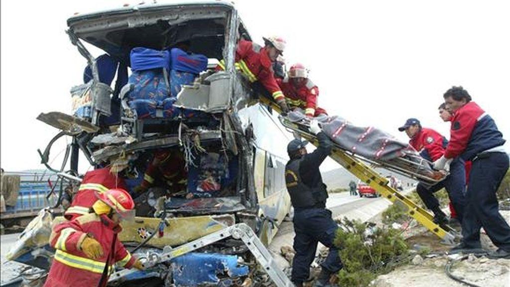 Miembros del Cuerpo de Bomberos y de la Policía Nacional de Perú extraen un cadáver del interior de un bus destrozado hoy en el departamento de Arequipa (Perú). EFE