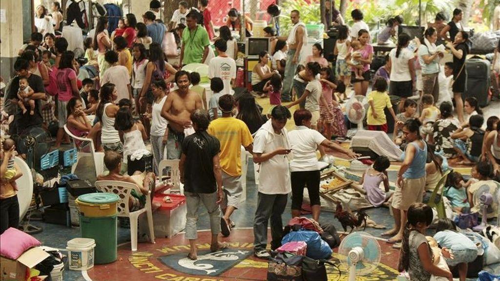 Varias personas permanecen en un centro de evacuación, luego que un enorme incendio arrasara al menos 700 chabolas de un barrio de Makati, al sur de Manila (Filipinas), hoy, 19 de abril de 2011. EFE