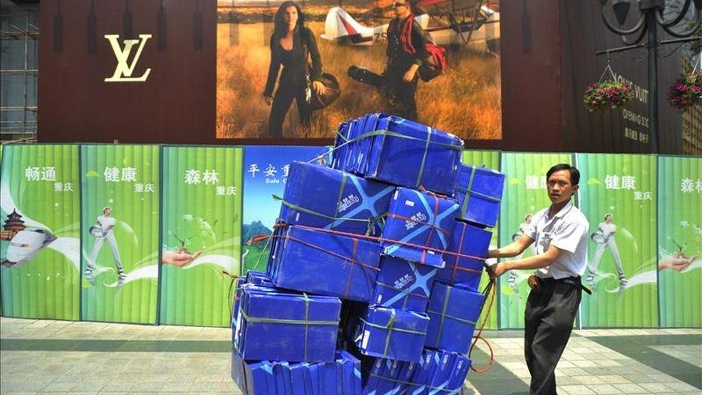 Un trabajador transporta una carga de Louis Vuitton al local donde en los próximos días se abrirá una de sus tiendas, en el área comercial de Chongqing, al suroeste de China. EFE/Archivo