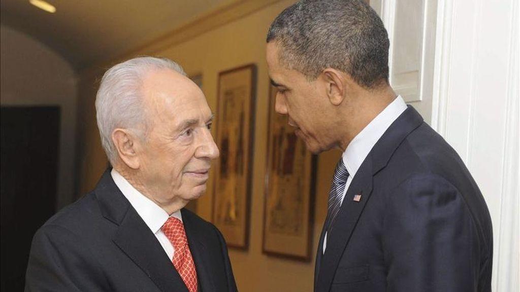 El presidente de los Estados Unidos, Barack Obama, (d), estrecha la mano del presidente israelí Shimon Peres (i) durante el encuentro que han mantenido en la Casa Blanca, Washington, Estados Unidos. EFE
