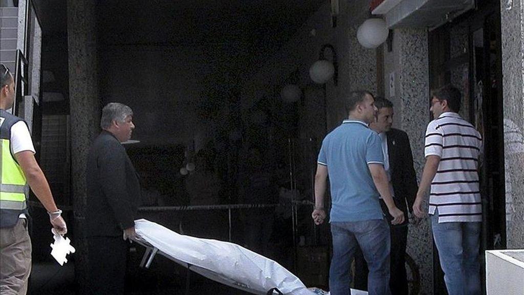 Operarios de los servicios funerarios retiran el cuerpo de una mujer que ha muerto hoy decapitada en un establecimiento de la avenida Juan Carlos I de Arona, en el sur de Tenerife. EFE