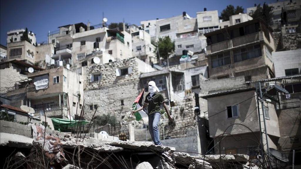 Un joven palestino enmascarado sostiene una bandera palestina durante una concentración de jóvenes palestinos en el barrio de Silwan, en Jerusalén Este, Israel, el 15 de abril de 2011. EFE/Archivo