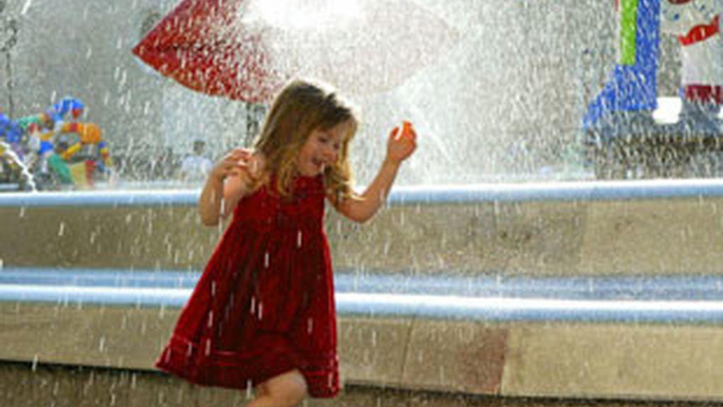 Una niña se refresca en una fuente. Fotos: EFE