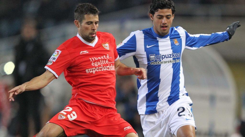 Carlos Vela  lucha por un balón con el defensa del Sevilla Jorge Andujar