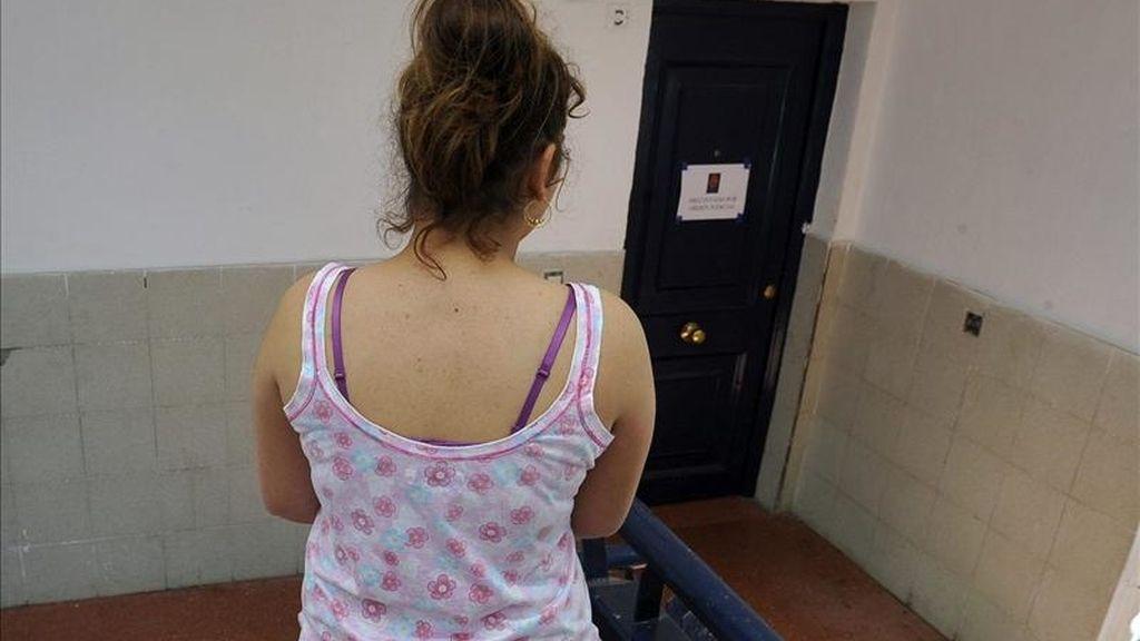 Una mujer delante de la puerta de la vivienda de la pareja detenida en Granada por su supuesta implicación en la muerte de un niño de seis años, hijo de unos vecinos del mismo bloque, cuyo cuerpo sin vida fue hallado esta madrugada en la parte posterior del inmueble. EFE
