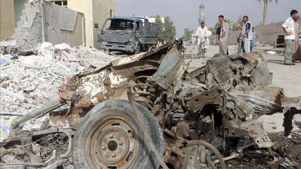 Iraquíes observan los restos de uno de los coches bomba que hicieron explosción en Faluya, Irak, ayer lunes, 11 de abril.Hoy otros dos nuevos ataques cerca de Bagdad han dejado 6 muertos. EFE