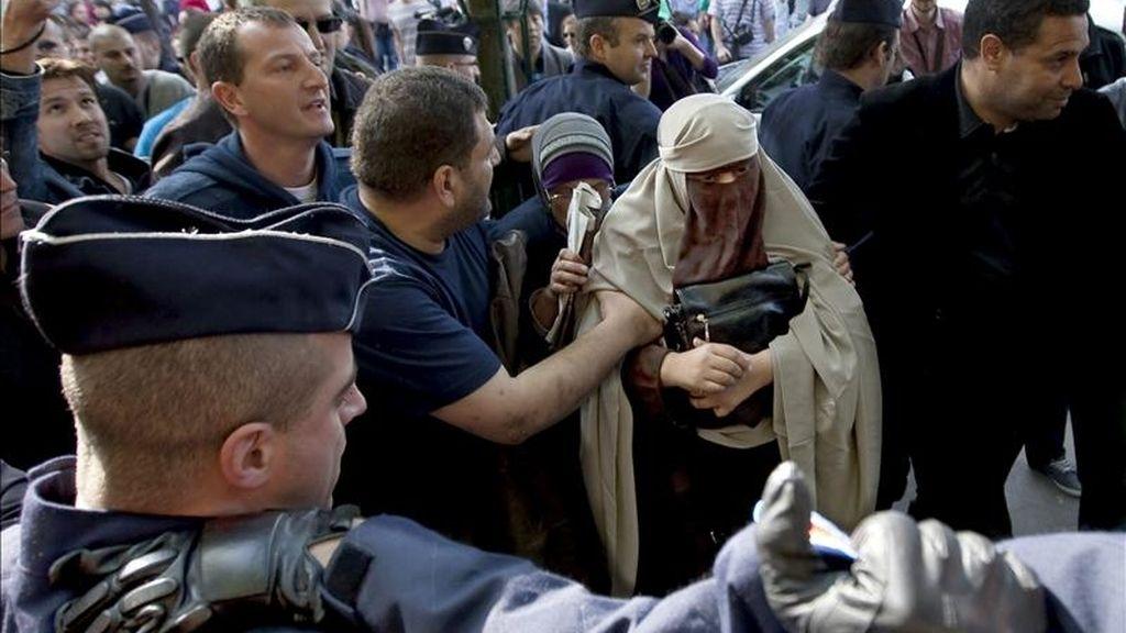 Kenza Drider (c), con niqab, es detenida por la policía francesa tras atender a los medios delante de la catedral de Notre Dame, en París, Francia. EFE