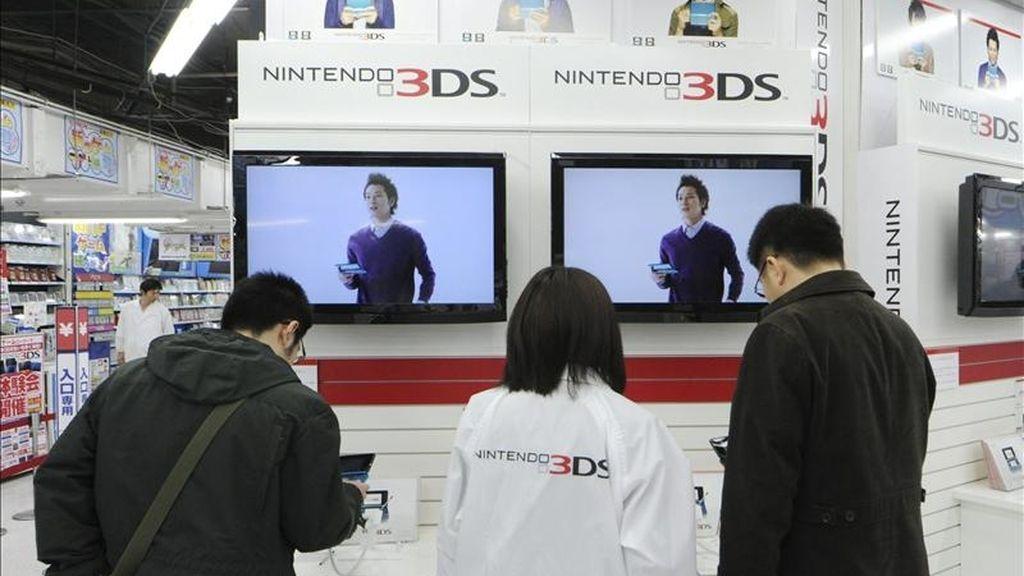 Un par de clientes prueban la nueva videoconsola portátil Nintendo 3DS en una tienda de electrónica del centro de Tokio (Japón). EFE/Archivo