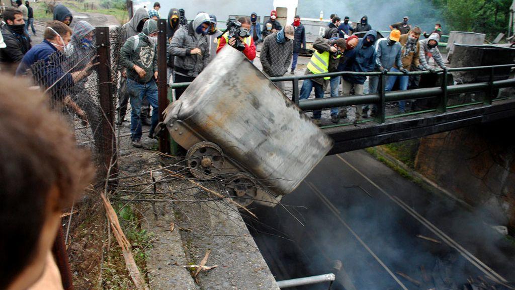 Un grupo de mineros lanza desde un puente a la carretera contenedores incendiados, en las inmediaciones del pozo Barredo, de Hunosa
