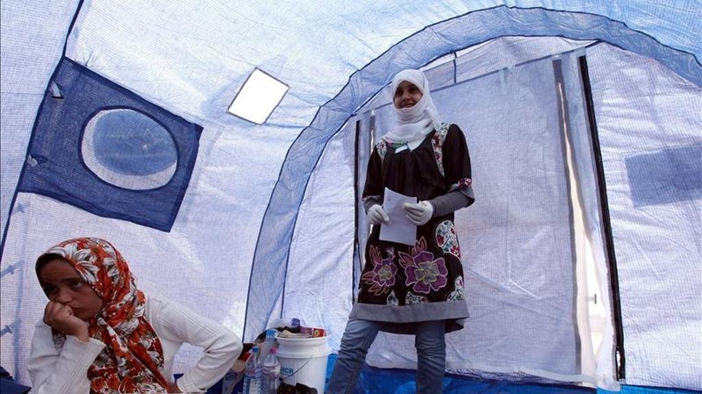 Una mujer libia y su familia, que huyen de la violencia producida cerca a la ciudad occidental libia de Nalut, habla dentro de una tienda de campaña en un campamento de refugiados abierto por parte de la organización Luna Roja en Ramada, a unos 25 km de la frontera sur de Libia, en Dehiba (Túnez). EFE/Archivo