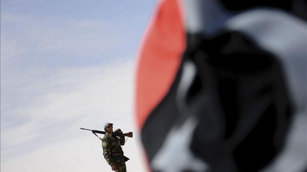 Una bandera libia pre-Gadafi situada ante un soldado libio vigilante desde un punto de control, en la localidad de Ajdabiya. EFE/Archivo