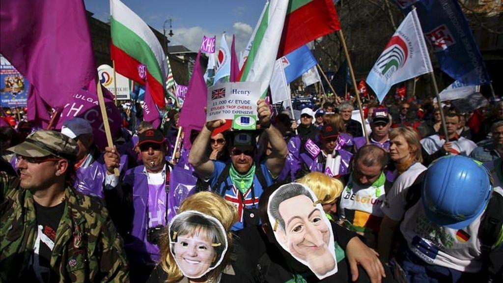 Un par de asistentes con caretas de la canciller alemana, Angela Merkel, y el presidente francés, Nicolas Sarkozy, participan junto a sindicalistas de toda Europa en una protesta hoy en Budapest. EFE