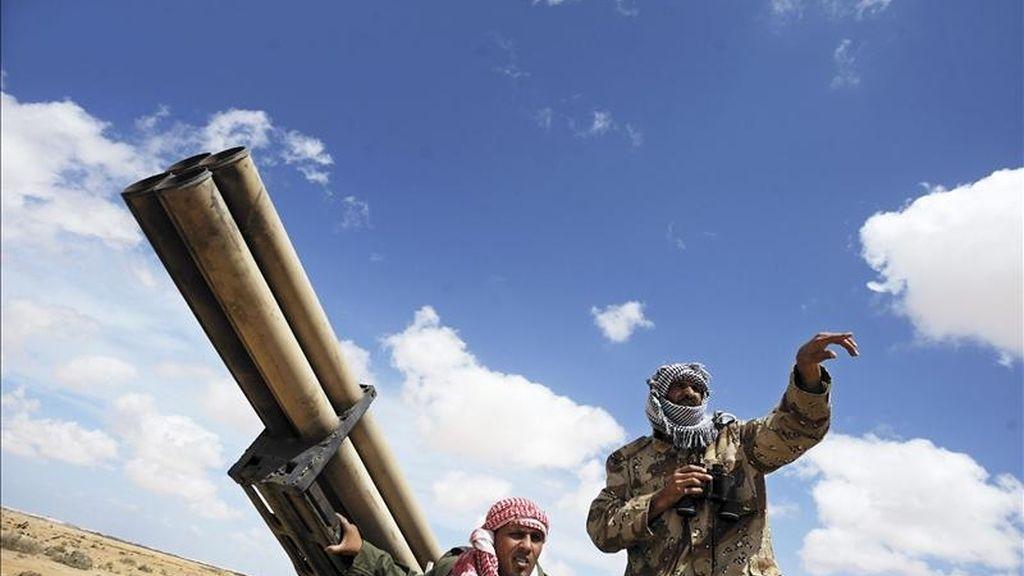 Soldados rebeldes libios conversan detrás de un lanzamisiles en un punto de control en la localidad de Ajdabiya, Libia. EFE