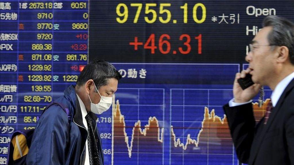 Un par de ciudadanos pasan delante de una pantalla que muestra información bursátil en Tokio (Japón). EFE/Archivo