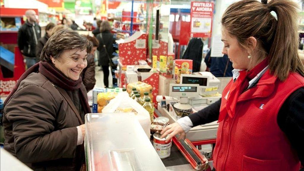 En la imagen, una cajera atiende a una clienta en un supermercado. EFE/Archivo
