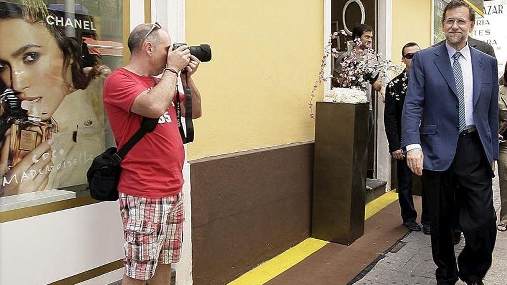 Un turista fotografía al presidente del Partido Popular (PP), Mariano Rajoy (d), durante un paseo por la capital tinerfeña tras intervir en un acto con empresarios y trabajadores autónomos de la isla. EFE
