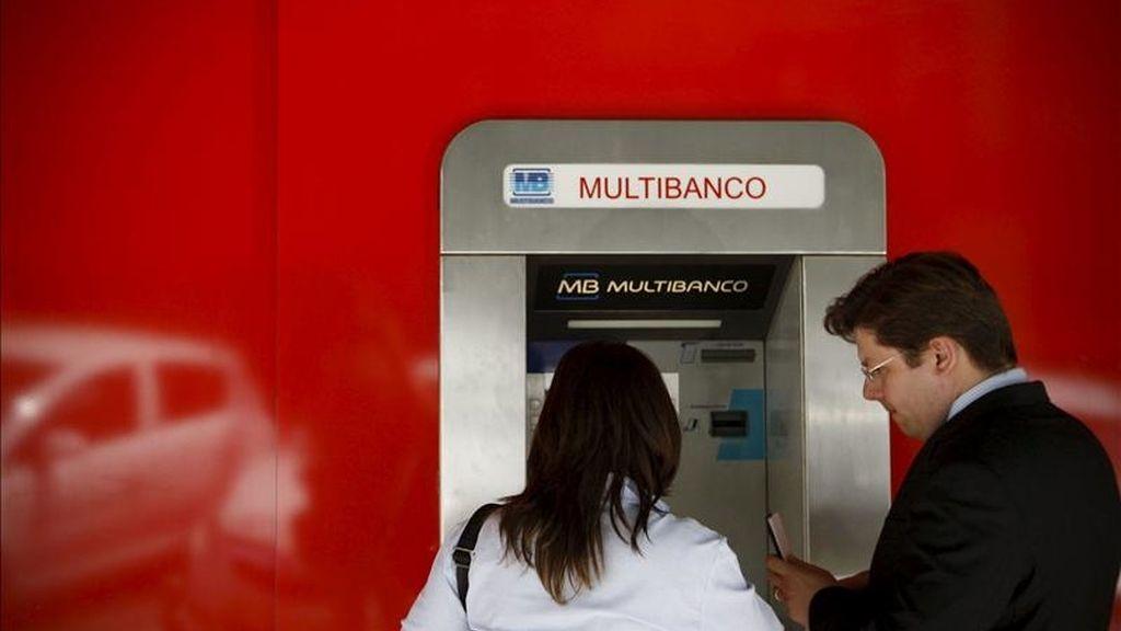 Una pareja saca dinero de un cajero automático, en Lisboa, Portugal. EFE